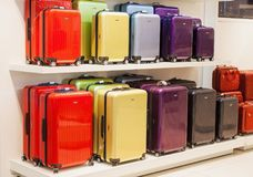 Modernt färgrikt metalliskt bagage som staplas på försäljning i shopping Arkivbild