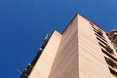 Modernt hörn för byggnadstegelstenvägg och blå sky Arkivfoto
