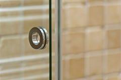 Modernt handtag på exponeringsglasdörr i badrum royaltyfri fotografi