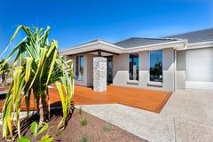 Modernt hus med ett träd och garaget med trä och stenya Arkivfoton