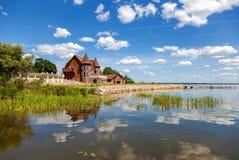 Modernt hus på sjön i solig dag för sommar Arkivbild
