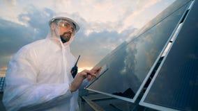 Modernt innovativt branschbegrepp Mannen arbetar på solpaneler bakgrund, slut upp arkivfilmer