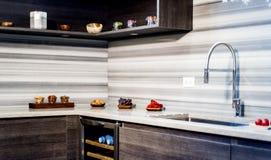 Modernt inre kök med bruna grundköksskåp och vita väggköksskåp Arkivbild