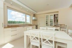 Modernt kök med den stora vita tabellen Arkivbild