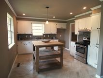 Modernt kök med den vita kabinetter och ön arkivbild