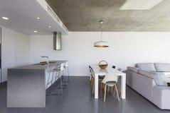 Modernt kök med grå färggolvet och vitväggen arkivbild