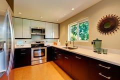 Modernt kök med vita countertops, vit och bruna nya kabinetter. Fotografering för Bildbyråer