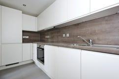 Modernt kök med naturlig stenworktop och tegelplattor i whi Arkivbilder