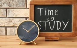 """Modernt klocka och svart tavla med uttryck \ """"Tid att studera \"""" på trätabellen Grungebakgrund f?r dina publikationer fotografering för bildbyråer"""
