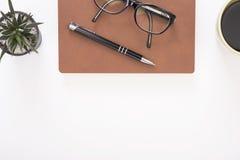 Modernt kontorsskrivbord med anteckningsboken, pennan, den pappers- boken och kaffekoppen arkivfoton