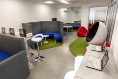 Modernt kontorsutrymme med skrivbord och bärbara datorer; vardagsrumutrymme i bakgrunden Arkivfoton
