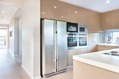 Modernt kylskåp i det lyxiga köket med mikrovågugnar arkivfoton