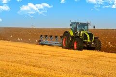 Modernt lantbruk med traktoren i plogat fält royaltyfri foto