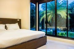 Modernt ledar- sovrum med breda glass fönster i aftonen Arkivbild