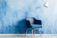 Modernt mörker - lampa för blå stol och för vit metall mot ombrevägg I arkivbild