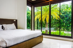 Modernt minimalist sängrum med breda glass fönster Royaltyfria Bilder