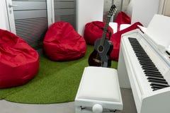 Modernt musik-rum, med den vita piano- och svartgitarren; röda sittkuddar i bakgrunden Royaltyfria Bilder