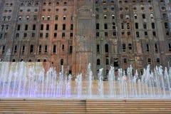 Modernt parkera med vattenspringbrunnar framme av en övergiven byggnad arkivbilder