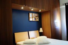 Modernt rum med den mörka marinblåa väggen och trägarderoben arkivbilder