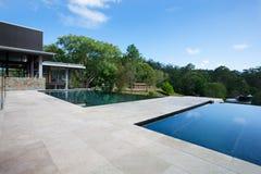 Modernt simma område med golvtegelplattor omkring i en skog arkivfoto