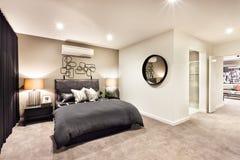 Modernt sovrum med en runt spegel och hall arkivbild