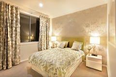 Modernt sovrum med konungformatsäng som är upplyst vid tabelllampor Fotografering för Bildbyråer