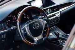 Modernt styrhjul med träbeståndsdelar och metalliska kromdelar i designen av en dyr Lexus bil på bakgrunden av arkivfoto