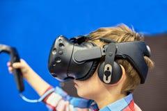 Modernt teknologi-, dobbel- och folkbegrepp - pojke i virtuell verklighethörlurar med mikrofon eller exponeringsglas som 3d spela royaltyfri foto