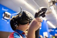 Modernt teknologi-, dobbel- och folkbegrepp - pojke i virtuell verklighethörlurar med mikrofon eller exponeringsglas som 3d spela arkivbild