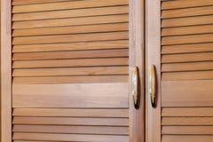 Modernt träkabinett i klassisk lantlig stil Detaljer av garderobfallet med slutareplankadörrar Inre för landshus Arkivfoton