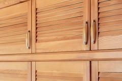 Modernt träkabinett i klassisk lantlig stil Detaljer av garderobfallet med slutareplankadörrar Inre för landshus Royaltyfri Fotografi