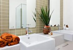 Modernt tvättande område, inklusive en orange färghandduk med silver royaltyfri bild
