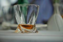 Modernt utsmyckat whiskyexponeringsglas med den guld- alkoholdrycken på en vit borddukyttersida som ett symbol av att dricka alko arkivfoto
