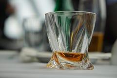 Modernt utsmyckat whiskyexponeringsglas med den guld- alkoholdrycken på en vit borddukyttersida som ett symbol av att dricka alko arkivbilder