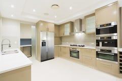 Modernt vitt kök i nytt lyxigt hem Arkivbild