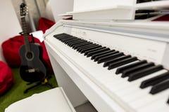 Modernt vitt pianotangentbord i fokus, svart gitarr och röda sittkuddar i bakgrunden Arkivbild