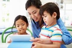 Moderportionbarn med läxa genom att använda den Digital minnestavlan Arkivbild