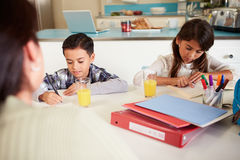Moderportionbarn med läxa på tabellen royaltyfria bilder