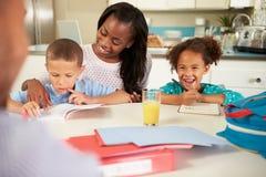 Moderportionbarn med läxa på tabellen royaltyfri foto
