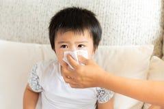 Moderportiondottern blåser hennes näsa hemma i vardagsrummet arkivfoton