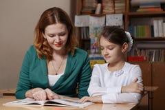 Moderportionunge efter skola förskolebarnet som gör läxa med hjälp av, handleder hem- undervisningbegrepp arkivfoto