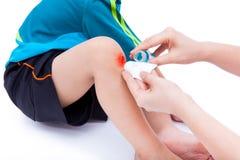 Moderrengöringen och ger första hjälpen på såret Arkivfoton
