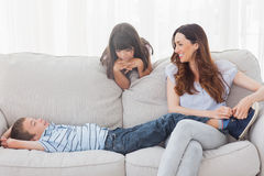 Modersammanträde med hennes barn på soffan Royaltyfri Bild
