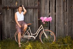 Modersammanträde på den beigea retro cykeln royaltyfria bilder