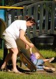 Moderskap behandla som ett barn glida ner glidbanan royaltyfria bilder