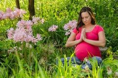 Moderskapyoga i en blommaträdgård/en äng Royaltyfri Bild