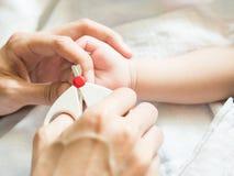 Modersnittet behandla som ett barn fingret spikar försiktigt Royaltyfri Fotografi