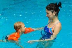 Moderundervisning behandla som ett barn pojken för att simma Arkivbild
