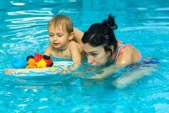 Moderundervisning behandla som ett barn pojken för att simma royaltyfri foto