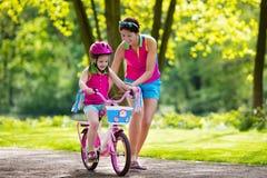 Moderundervisningbarn som rider en cykel royaltyfria foton
